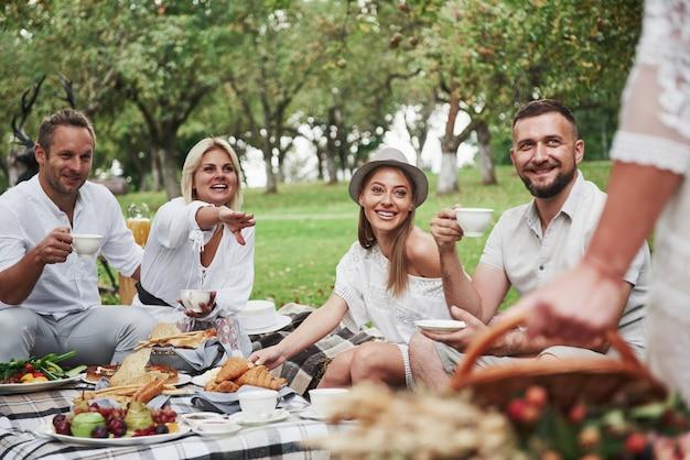 As pessoas olham para mulher. grupo de amigos adultos descansar e conversar no quintal do restaurante na hora do jantar