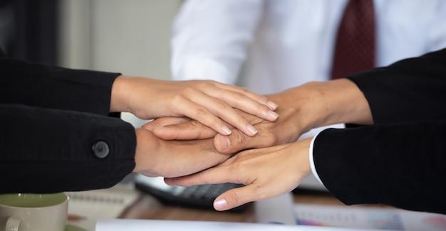 As pessoas que juntam as mãos demonstram trabalho em equipe.