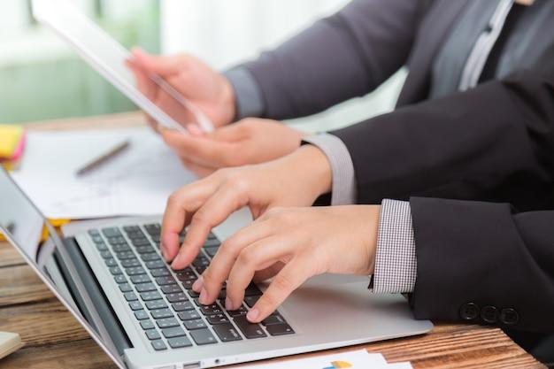 As pessoas que trabalham em uma mesa de madeira com um laptop e um tablet