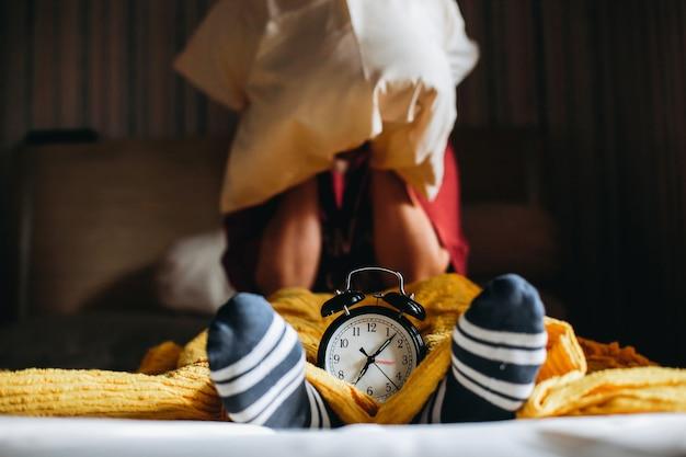 As pessoas são acordadas do sono pelo despertador marcando 7 horas e cobrem os ouvidos com travesseiros