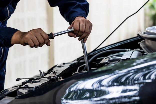 As pessoas são consertar um carro use a mão e uma chave de fenda para o trabalho. seguro e confiante na condução.