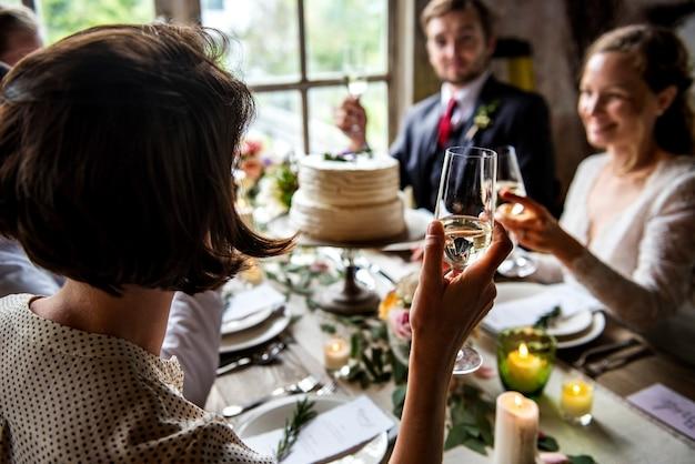 As pessoas se agarram a taças de vinho na recepção de casamento com a noiva e o noivo