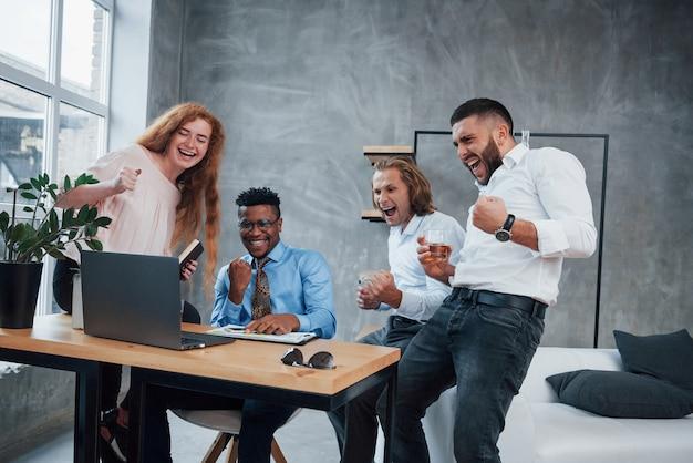 As pessoas se alegram com a vitória. grupo de trabalhadores de escritório multirracial em roupas formais falando sobre tarefas e planos