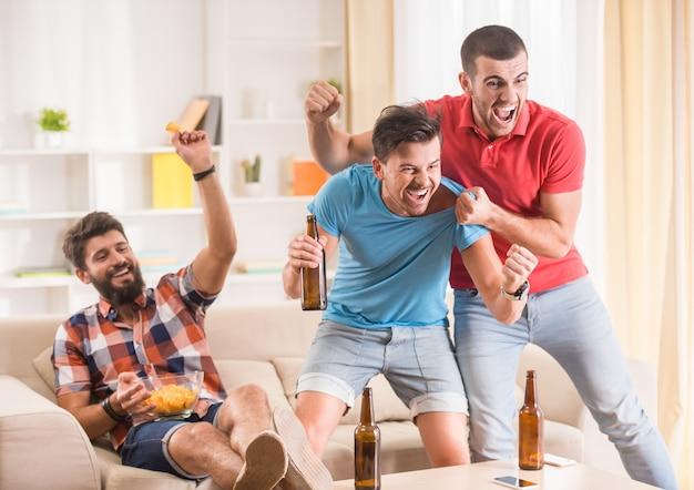 As pessoas se alegram com um gol marcado em um apartamento.