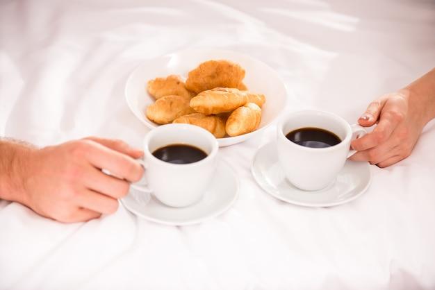 As pessoas sentam-se em casa e bebem café com croissants.