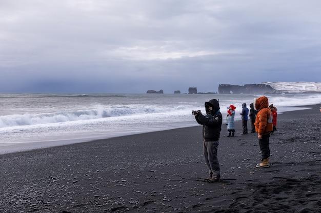 As pessoas tiram fotos do panorama e das ondas do inverno do oceano atlântico e da praia reynisfjara choni