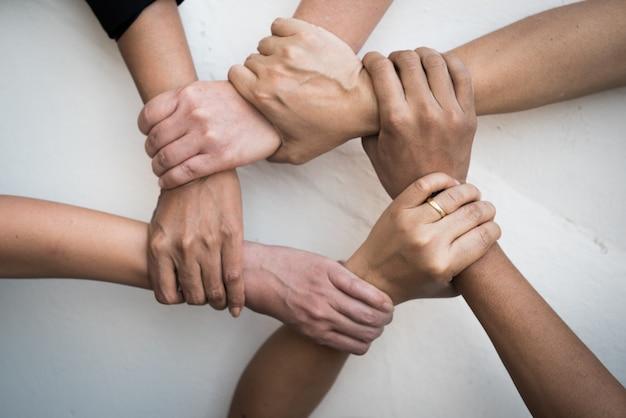 As pessoas uniram as mãos juntas no trabalho em equipe.