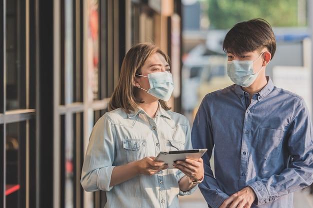 As pessoas usam máscara para proteger o coronavírus falando de negócios com a tecnologia de tablet
