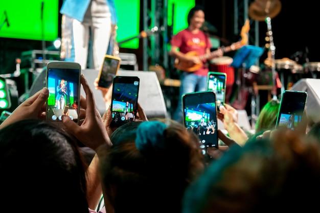 As pessoas usam telefones celulares para viver ou tirar fotos em shows, com luzes brilhantes à noite.