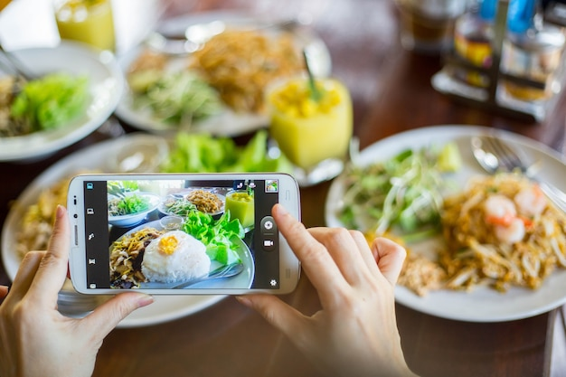As pessoas usam um telefone inteligente para tirar comida de foto. comida de café da manhã.