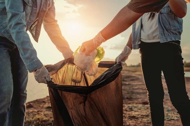 As pessoas voluntárias mantendo o lixo plástico e garrafa de vidro em saco preto no rio park no pôr do sol