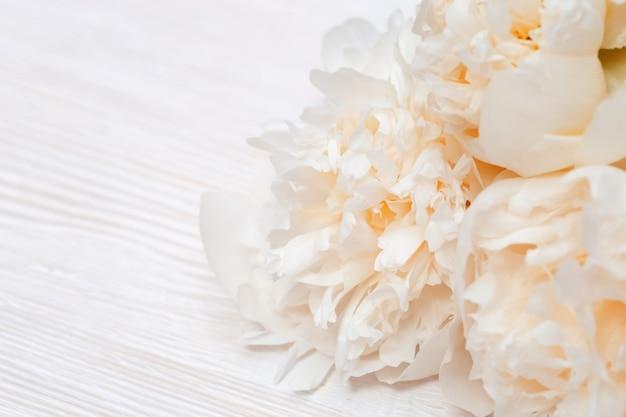 As pétalas da peônia das flores fecham-se acima na madeira clara.