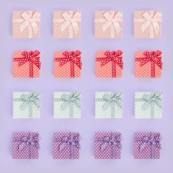 As pilhas de caixas de presente coloridas pequenas com fitas encontram-se em um fundo violeta. minimalista plana leigos padrão de vista superior