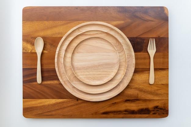 As placas de madeira lacadas redondas são empilhadas em várias camadas. ao lado, há colheres e garfos, bem como o pano de fundo da madeira de acácia com belos padrões de madeira.