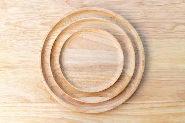 As placas redondas de madeira e laca de borracha são empilhadas em várias camadas e colocadas sobre uma tábua de madeira no conceito de utensílio de cozinha.