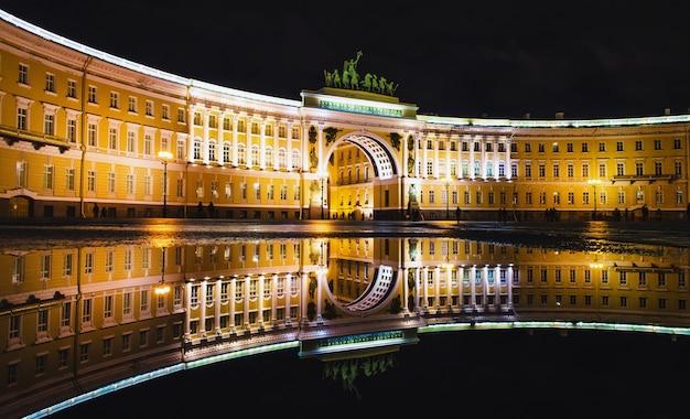 As poças da praça do palácio e a noite nevsky prospekt iluminam as casas antigas de são petersburgo