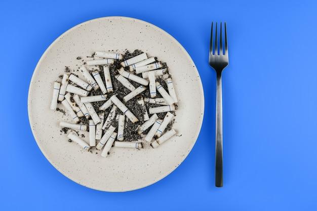 As pontas de cigarro em uma placa e a forquilha em um fundo azul copiam o espaço. cigarros para o almoço.