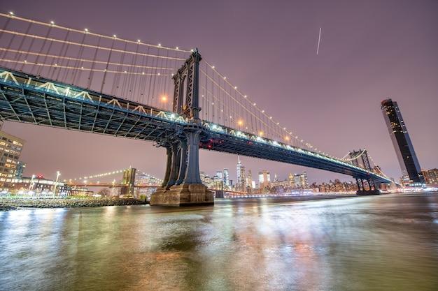 As pontes do brooklyn e de manhattan à noite do broolyn bridge park, na cidade de nova york no inverno.