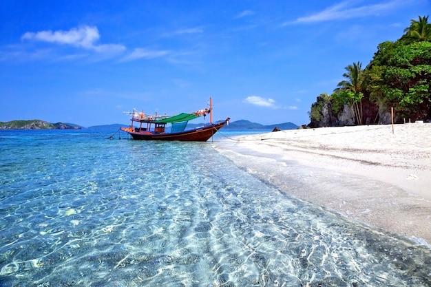 As praias de mar tropical com barcos e lindo céu.
