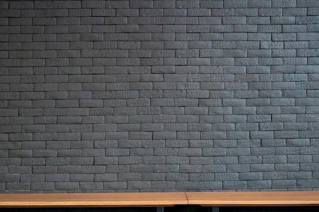 As prateleiras de madeira superiores vazias e a parede de tijolo velha texture o fundo.