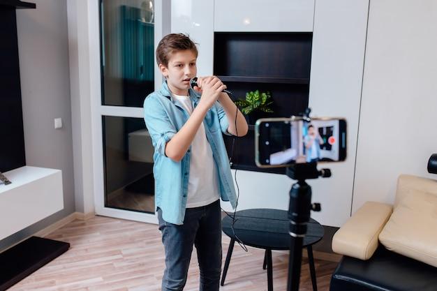 As pré-adolescentes em casa cantam no microfone. jovem americano trabalhando como influenciador da web,