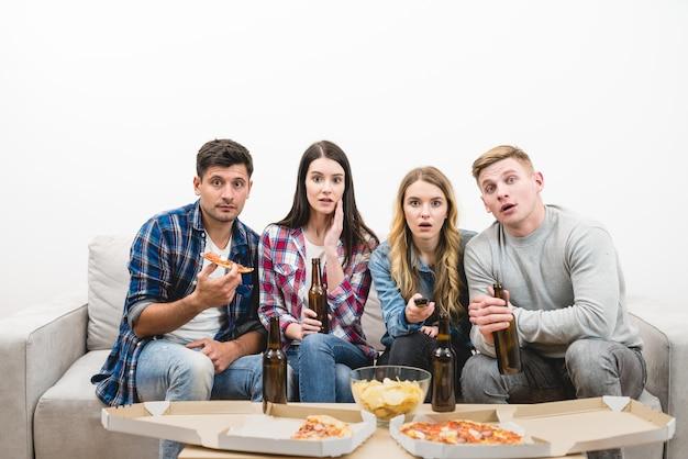 As quatro pessoas assistem tv com uma pizza e uma cerveja no fundo branco