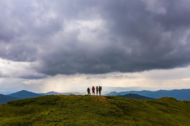 As quatro pessoas ativas em uma montanha contra a pitoresca vista da nuvem
