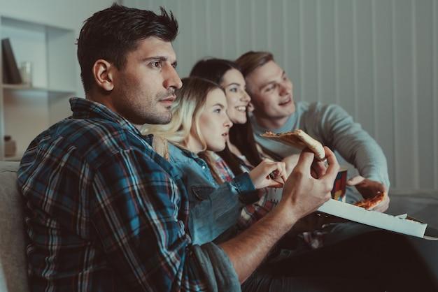 As quatro pessoas com uma pizza assistem a um filme no sofá