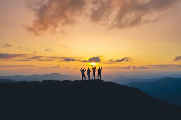 As quatro pessoas de pé na bela montanha ao fundo do nascer do sol