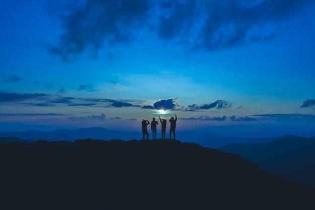As quatro pessoas em pé na bela montanha ao fundo da lua