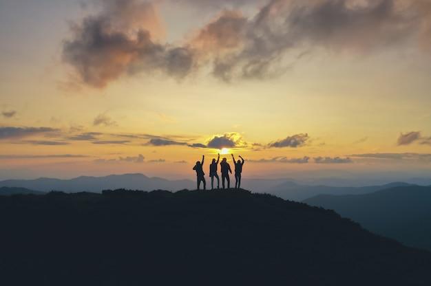 As quatro pessoas em pé na bela montanha no fundo do pôr do sol