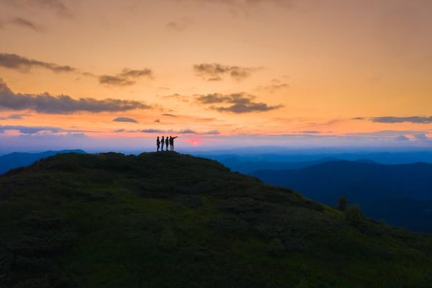 As quatro pessoas em pé na montanha pitoresca ao fundo do nascer do sol