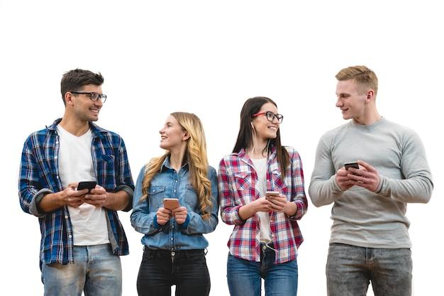 As quatro pessoas felizes com telefones em pé no fundo da parede branca