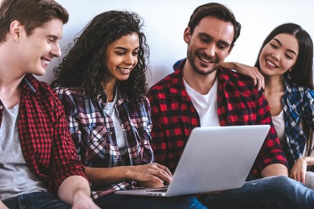 As quatro pessoas felizes com um laptop sentado no chão