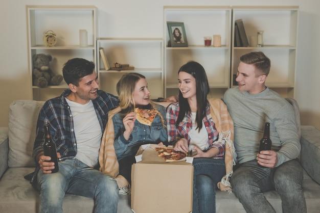 As quatro pessoas felizes com uma pizza e uma cerveja assistem a um filme no sofá
