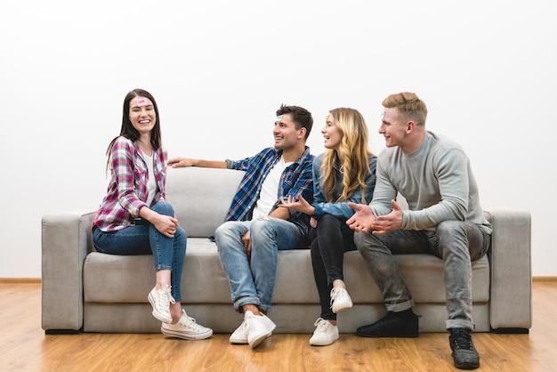As quatro pessoas felizes no sofá jogam no fundo da parede branca