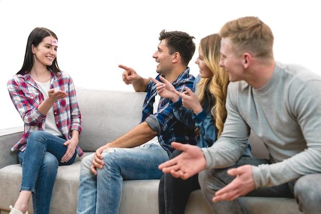 As quatro pessoas felizes no sofá jogam o jogo no fundo branco