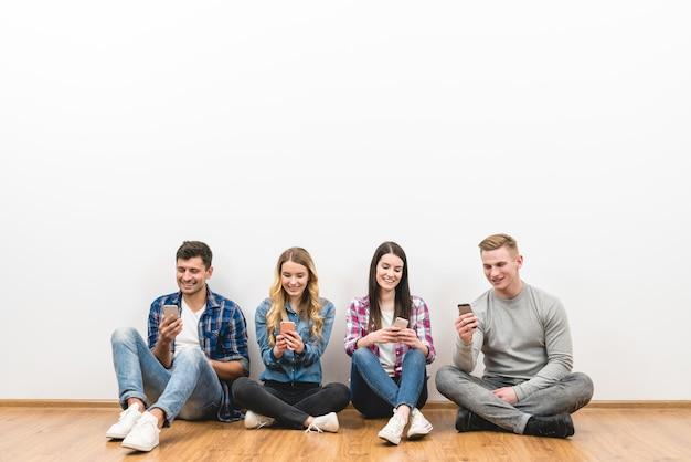 As quatro pessoas felizes sentam no chão e telefonam no fundo branco