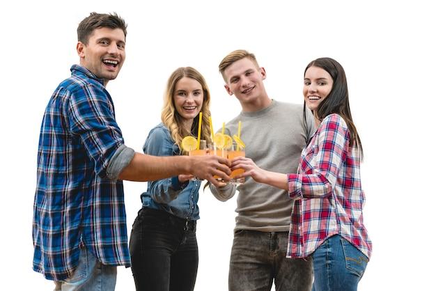 As quatro pessoas positivas tilintam de taças em um fundo branco