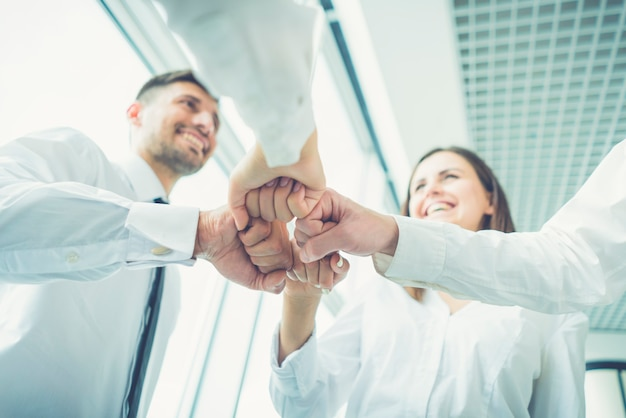 As quatro pessoas sorriem gesticulando com o punho