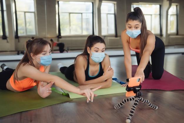 As raparigas seguem de perto o professor online através do smartphone. meninas com máscaras protetoras