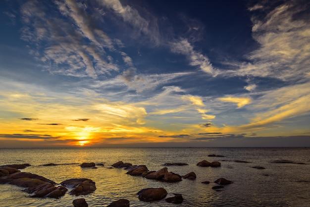 As rochas no mar com o céu do sol