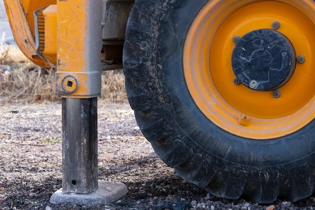 As rodas laranja cobertas de trator de lama. agronomia, conceito agrícola. agricultura. perto de uma grande roda amarela de um trator com pneu preto, máquinas agrícolas. pé hidráulico da grua.