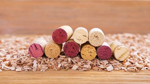 As rolhas de cortiça com mancha vermelha encontram-se em uma pilha no fundo das lascas de madeira. fon de madeira natural com montes de rolhas de vinho tinto e branco. foco seletivo. copie o espaço.