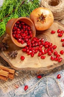 As romãs da vista frontal espalharam sementes de romã em sementes de anis em uma tigela em uma árvore de madeira tábua de palha fio de canela em fundo azul e branco
