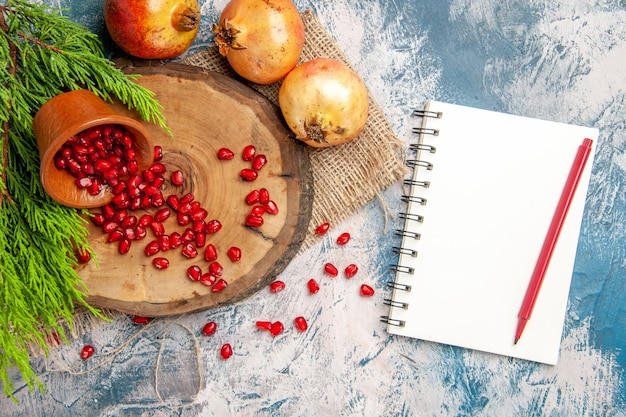 As romãs de cima espalharam sementes de romã em uma tigela na madeira da árvore em um caderno com uma caneta no fundo branco e azul.