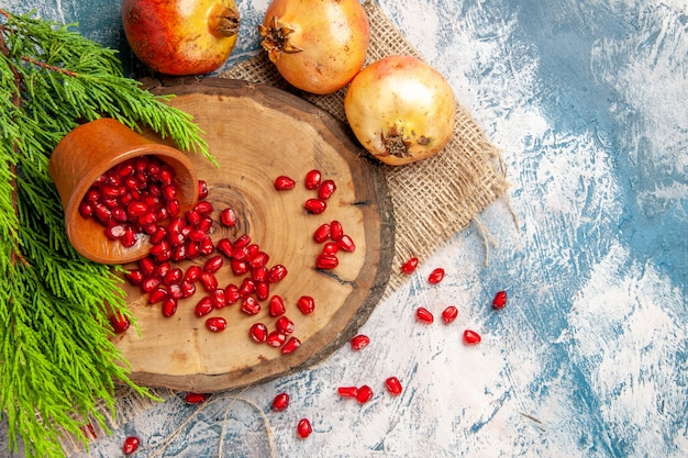 As romãs de cima espalharam sementes de romã em uma tigela na placa de madeira da árvore no fundo branco-azulado