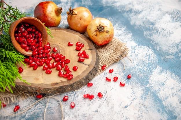 As romãs de frente espalharam sementes de romã em uma tigela de madeira em uma tábua de corte redonda em um fundo branco e azul.