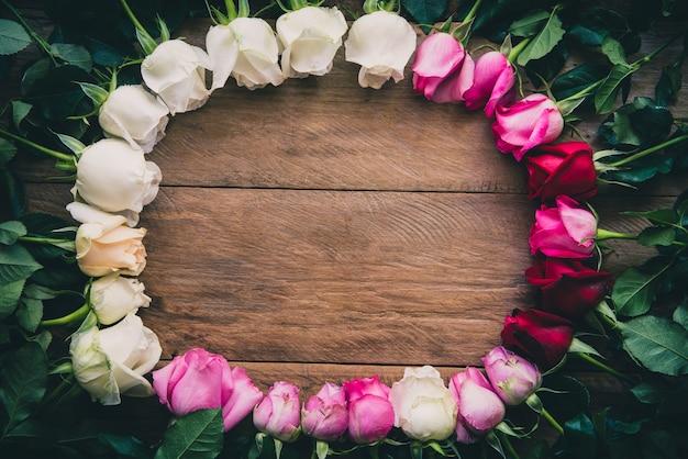 As rosas coloridas alinharam em um assoalho de madeira com espaço para escrever sua mensagem.