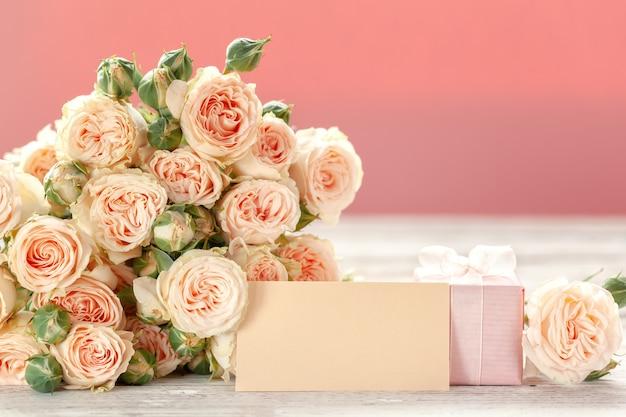 As rosas cor-de-rosa florescem e presente ou fundo cor-de-rosa atual da caixa.